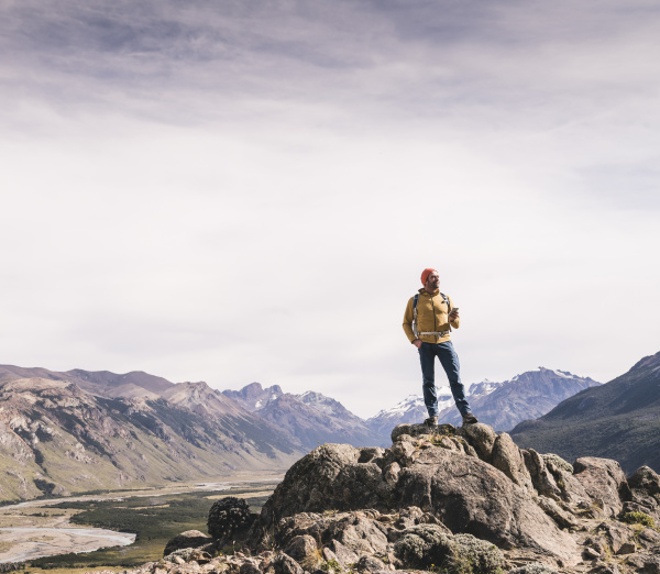 mature male hiker standing on rock
