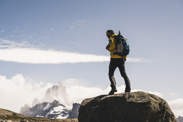 male hiker with backpack standing on