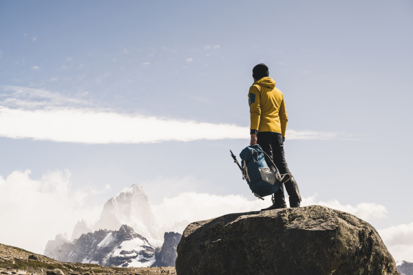 male hiker holding backpack while standing