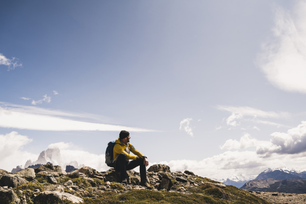 male hiker sitting on mountain against