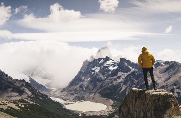 man looking at snowcapped mountain against