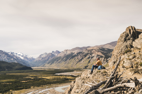 male hiker sitting on rock against