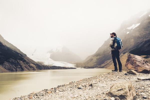 mature man standing at lakeshore during
