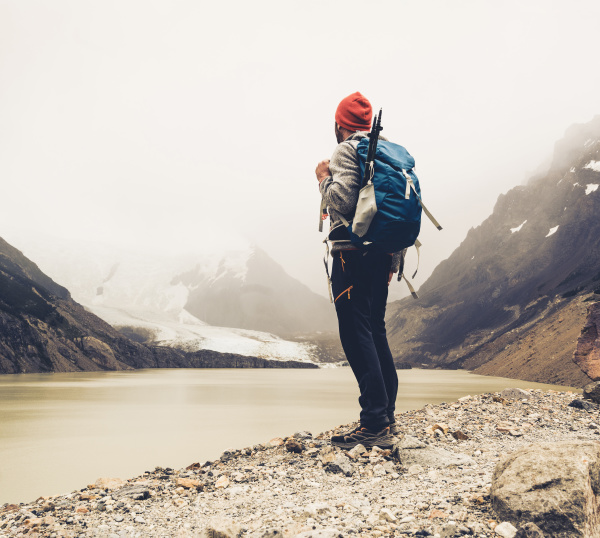 man with backpack standing by lake