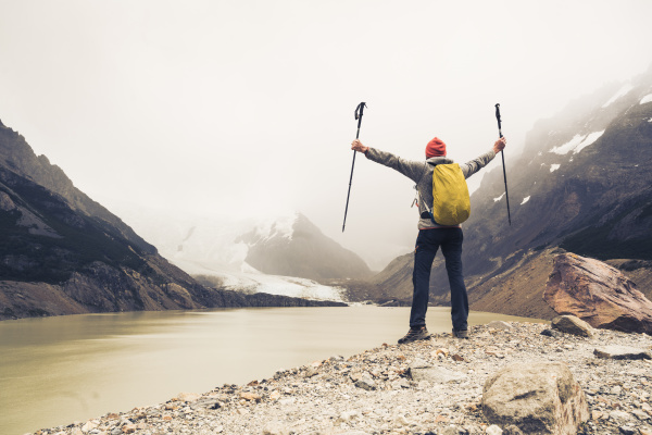 man with arms outstretched holding hiking