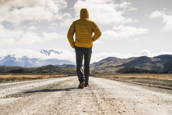 male hiker walking on dirt road