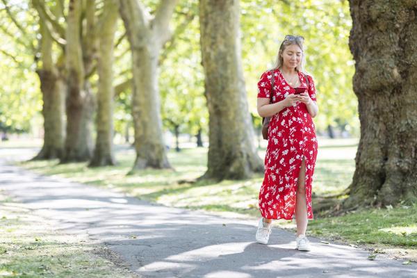 woman using smart phone while walking