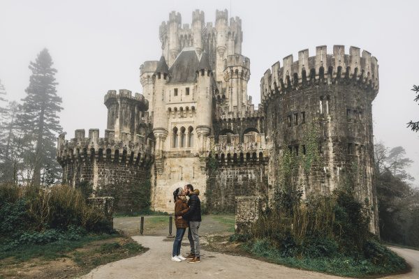 couple kissing while standing against butron