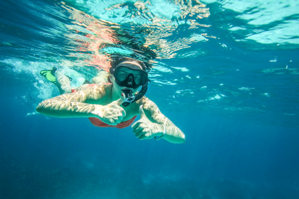 young woman snorkel holding two