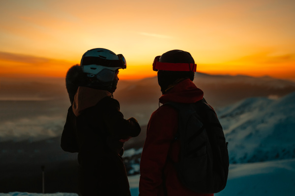 silhouette of two people wearing ski