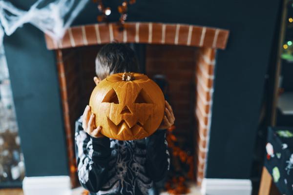 a boy holding a pumpkin head