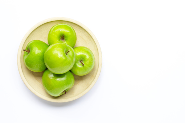 fresh green apples on pottery plate