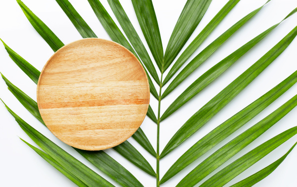 empty wooden plate on tropical palm
