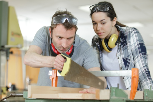 carpenter and apprentice working together in