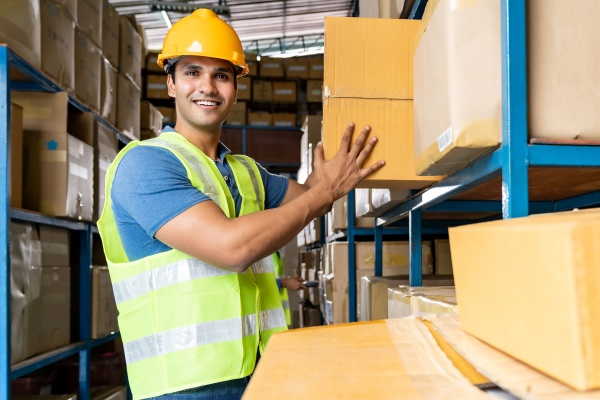 indian warehouse worker put cardboard box