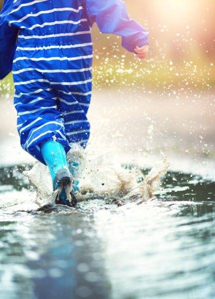 child walking in wellies in puddle