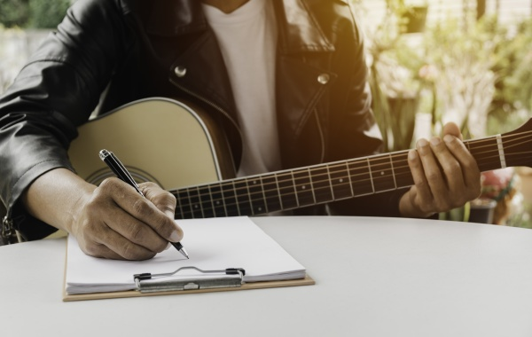 a song writer holding pen for