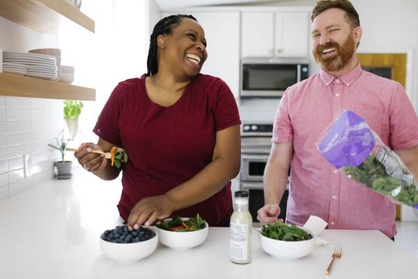 happy man and woman preparing salad