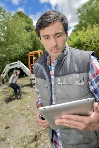 man stood in garden holding tablet