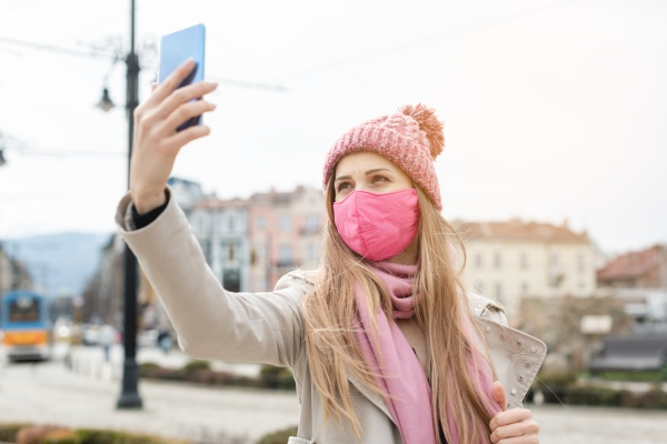 woman wearing corona mask making selfie