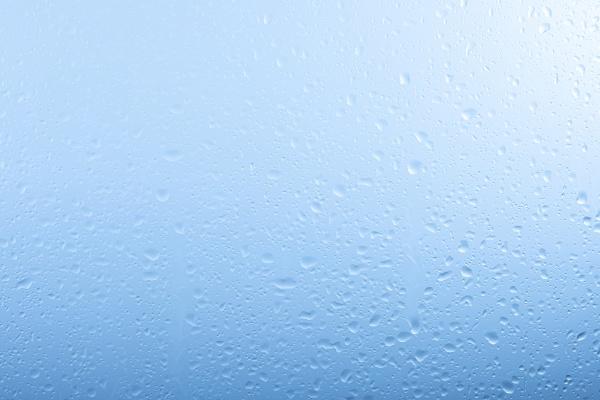 raindrops on glass window over grey