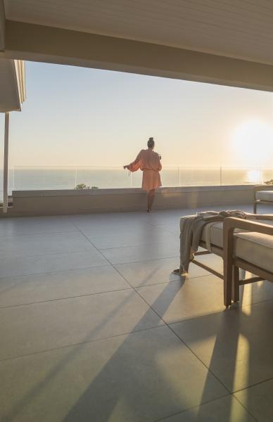 woman in bathrobe enjoying ocean sunset