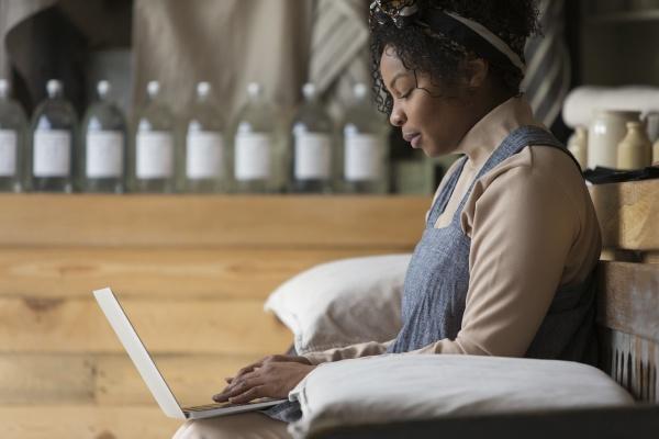 female shop owner using laptop on