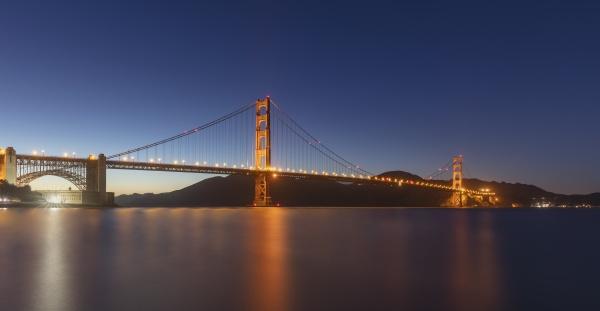 illuminated golden gate bridge over sea