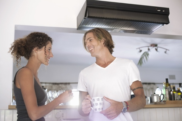 smiling couple holding coffee cup while