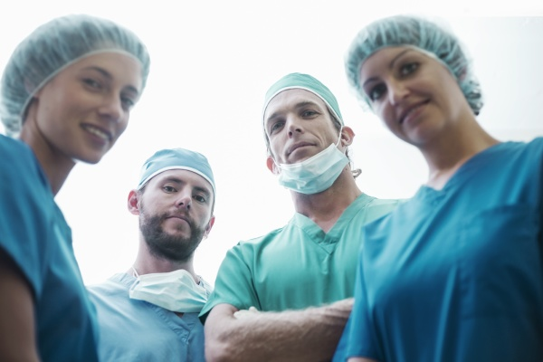 confident male and female surgeons standing