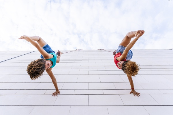 aerial dancers touching toes while hanging