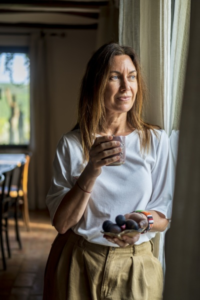 thoughtful female nutritionist holding drink and