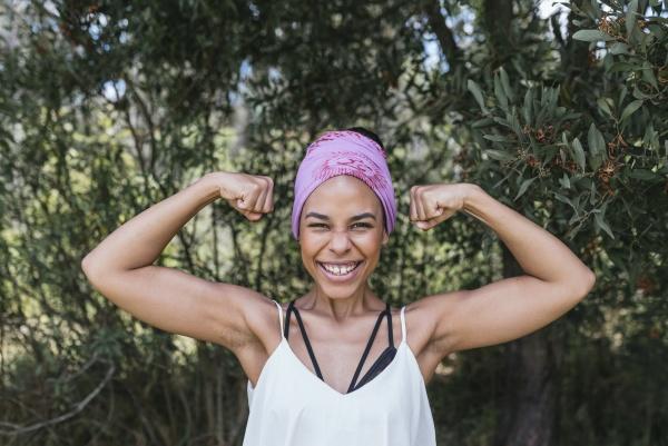 happy woman with purple bandana flexing