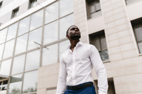 confident businessman looking away while standing