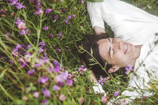 cheerful woman with eyes closed lying
