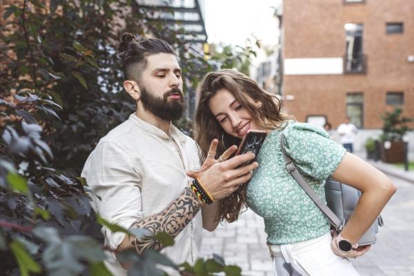 boyfriend gesturing while showing smart phone