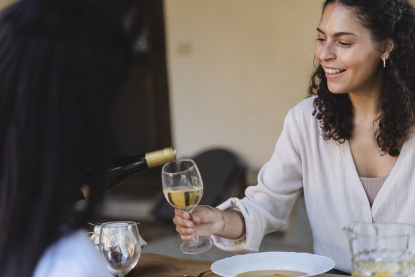 smiling woman holding wineglass while sitting