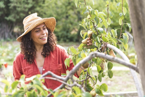 smiling woman looking at fresh pears