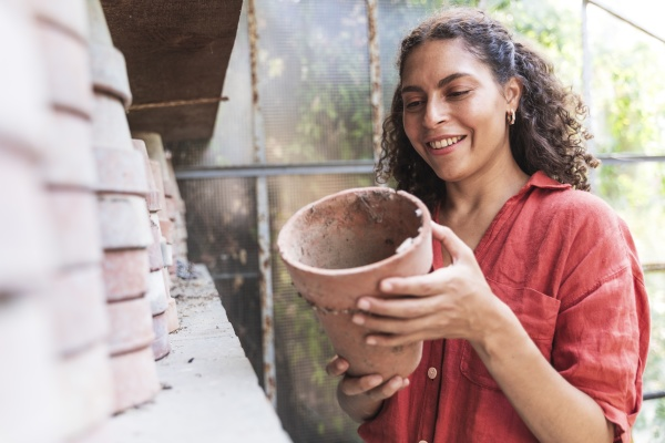 smiling woman holding pot while standing