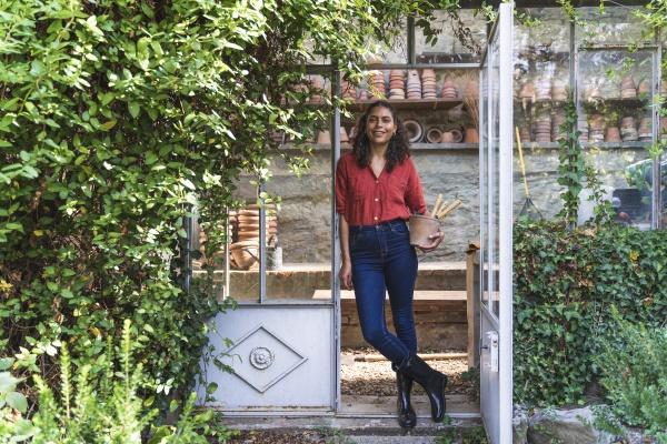 mature woman standing with gardening equipment