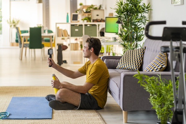 fitness trainer holding tripod with mobile