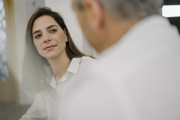 businesswoman listening to partner while sitting