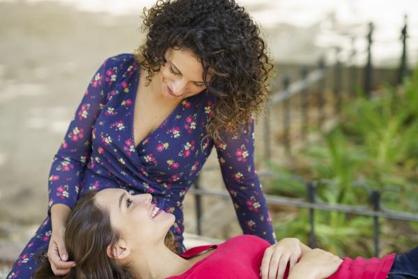 smiling girlfriend lying on woman lap