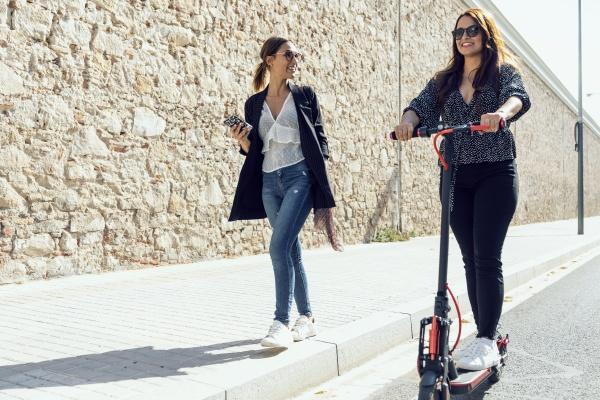 woman walking by friend riding push