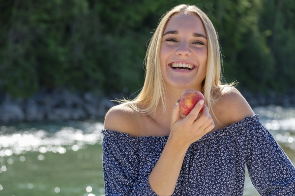 young woman with apple laughing while
