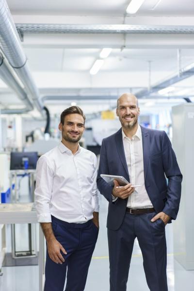 smiling mature businessman holding digital tablet