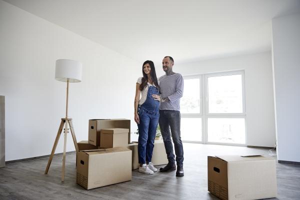 couple standing on floor with cardboard