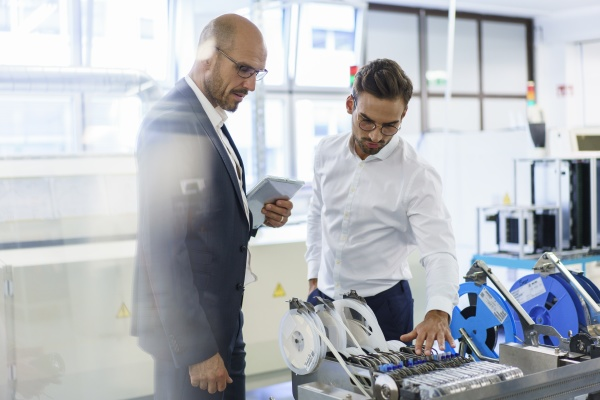 confident male technicians discussing over machinery