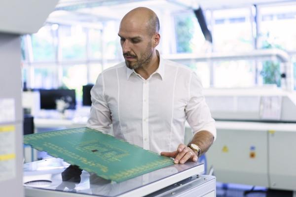 confident mature male technician examining large