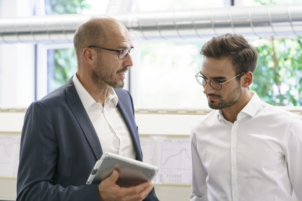 businessman discussing with male technician over